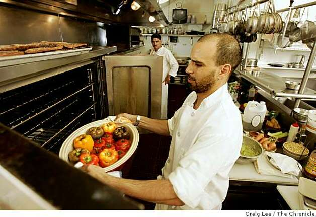 MOROCCAN14_307_cl.JPG Photo of Mourad Lalou putting a dish of Stuffed Bell Peppers with Ground beef and Lamb, with Tomato Sauce, in the convection oven to finish it off. Cooking with Moroccan chef, Mourad Lalou at his restaurant, Aziza at 5800 Geary Blvd. at 22nd. Story on Moroccan trinity of ingredients: tomatoes, eggplant and peppers.Event on 8/9/05 in San Francisco.Craig Lee / The Chronicle Photo: Craig Lee, The Chronicle