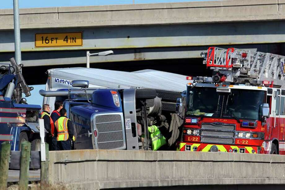 A wrecker crew and the San Antonio Fire Department work to upright an 18-wheeler tractor-trailer rig on the ramp connecting Loop 410 to U.S. 37 South. Around 9 a.m., the tractor-trailer flipped over while the driver was taking the exit from Loop 410 West onto U.S. 37 South, according to San Antonio police and fire officials. The driver was not thought to have major injuries. It was not immediately known how long the ramp would be closed, but a fire department spokeswoman said a wrecker to remove the truck had already been ordered about a half-hour after the crash occurred. (Tuesday November 29, 2011) JOHN DAVENPORT/jdavenport@express-news.net Photo: SAN ANTONIO EXPRESS-NEWS