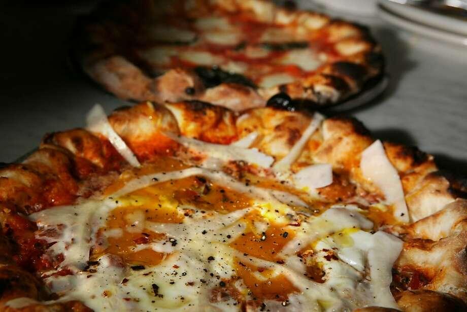 """A """"Purgatorio"""" pizza (foreground) - Spicy tomato sauce, 2 eggs, Pecorino Romano and a Marcherita (background) pizza - Tomato, fior di latte mozzarella, basil -  photographed at Pizzeria Delfina in San Francisco, Calif. on Sunday, December 28, 2008. Photo: Lea Suzuki, The Chronicle"""