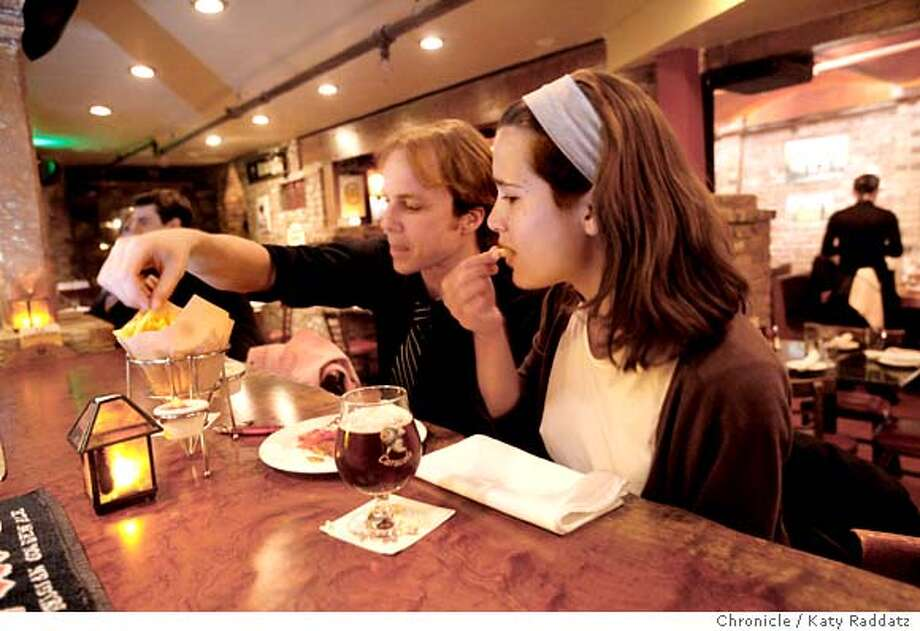 John Peterson, left, and Claire Scheidegger, right, enjoy a snack of fries at La Trappe, a Belgian restaurant and bar in North Beach, on Wednesday April 16, 2008, in San Francisco, Calif.  Photo by Katy Raddatz / San Francisco Chronicle  Ran on: 04-23-2008  John Peterson (left) and Claire Scheidegger share fries and beer at La Trappe in North Beach. Photo: KATY RADDATZ