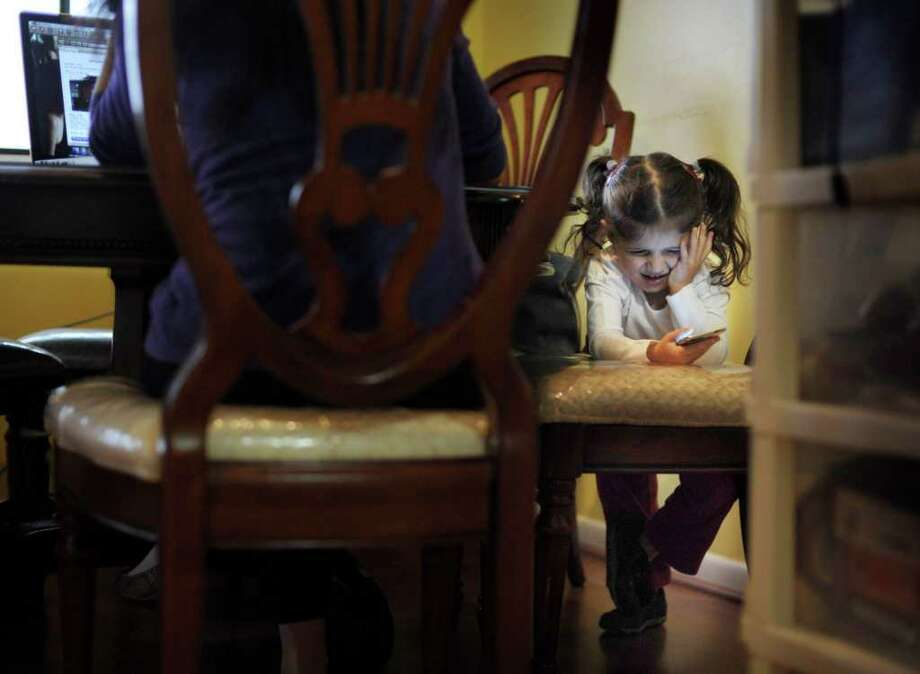 """Maggie Awad, 2, plays an app game on an iPod Touch at her home in Falls Church, Va.  """"She's learning and having fun,""""  said Maggie's mother, Paula Mansour.  """"I don t see any harm in that."""" Photo: MELINA MARA, WASHINGTON POST / The Washington Post"""