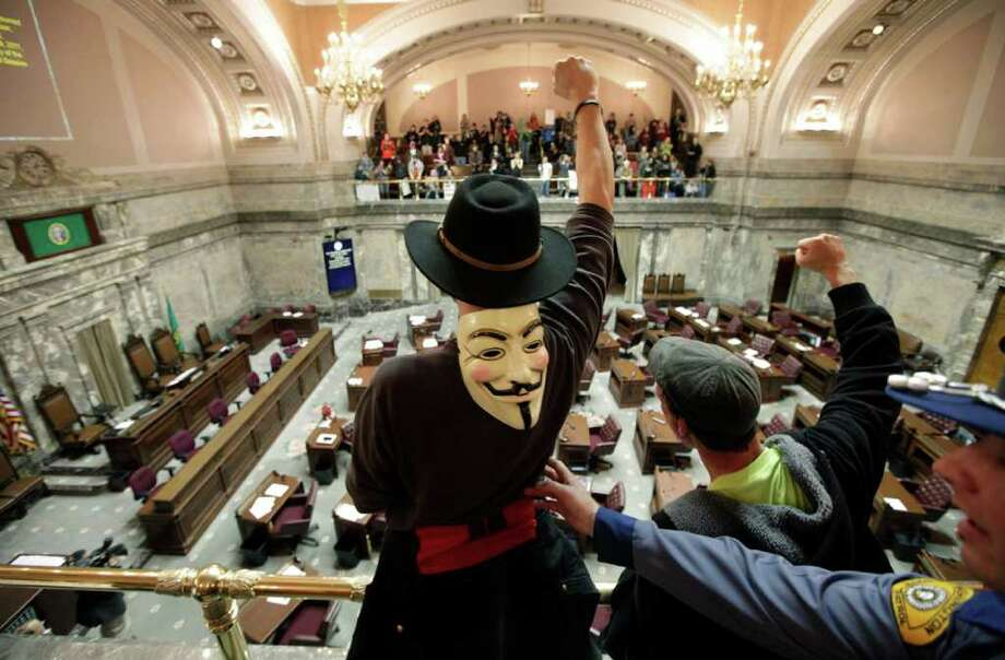 Protesters, including Justin Fisher, center, of Bellevue, Wash., demonstrate against budget cuts from the balconies of the House chamber inside the Capitol in Olympia, Wash., Monday, Nov. 28, 2011, on the first day of a special session of the Washington state legislature. The House was in recess at the time. Washington lawmakers beginning a 30-day special session were met by hundreds of protesters Monday, and a committee meeting focusing on solutions to the state's budget woes was abruptly halted amid a group's shouting. Photo: Ted S. Warren, AP / AP
