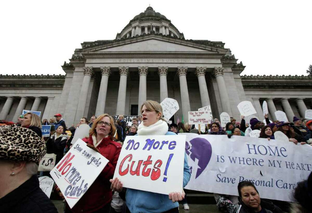 Protesters, including Regan Bailey, center left, and Heather McKimmie, center right, both of Seattle, demonstrate against budget cuts outside the Capitol in Olympia, Wash., Monday, Nov. 28, 2011, on the first day of a special session of the Washington state legislature.