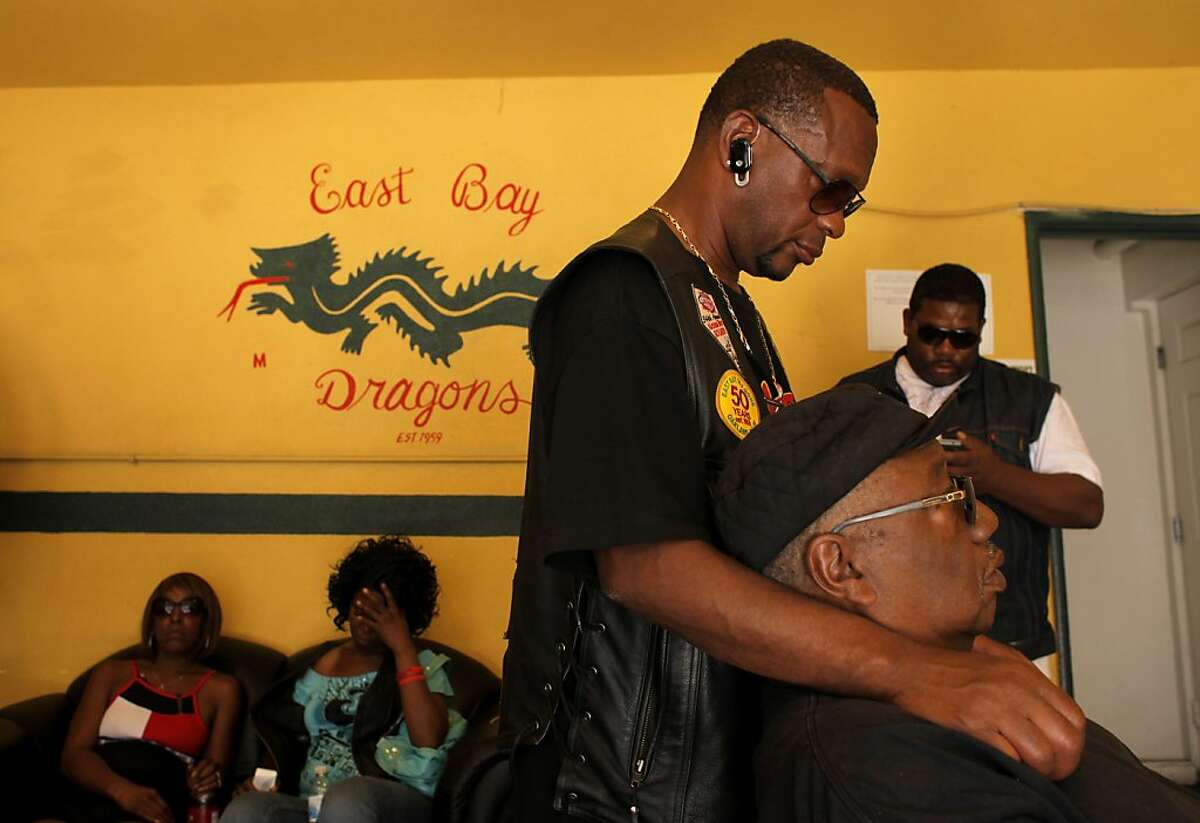 Members of the East Bay Dragons Motorcycle Club console each other as they mourn over the killing of their brother Hassan Sayyid also know as Ike, Monday September 28, 2011, at the club in Oakland, Calif. Sayyid, 40-years -old was shot to death by a suspect that walked into the clubs garage Sunday night as the members were watching television.