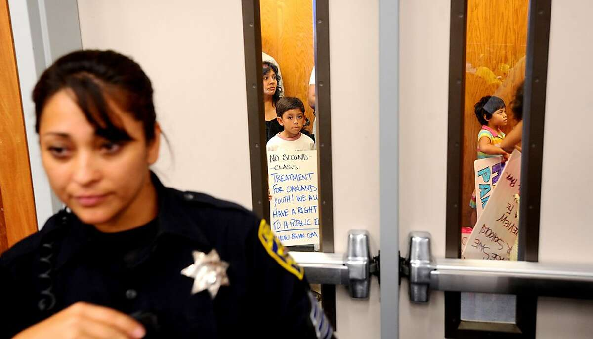 Outside an auditorium overflowing with angry parents, teachers and students, Saul De Anda, a 4th grader at Lazear Elementary School, waits to attend an Oakland Board of Education meeting on Tuesday, Sept. 27, 2011, in Oakland, Calif. About 40 students and parents waited up to an hour to get into the meeting and argue against closing schools.
