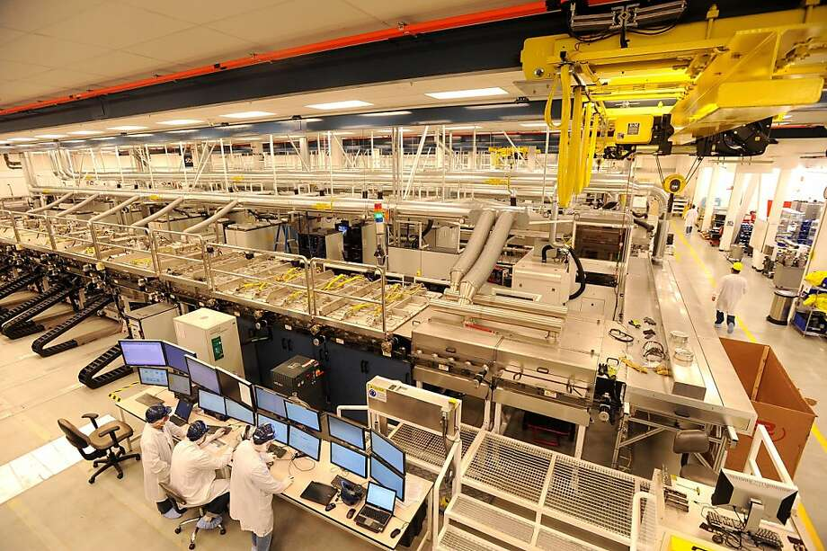 FILE - In a file photo dated Oct. 6, 2010, workers man a control bank at Solyndra's solar panel factory on in Fremont, Calif. The Silicon Valley company was the first renewable-energy company to receive a loan guarantee under the stimulus law, and the Obama administration frequently touted Solyndra as a model for its clean energy program. President Barack Obama visited the company's headquarters last year.(AP Photo/Noah Berger, File)  Ran on: 09-28-2011 Solyndra employees work last October at a control bank inside the solar panel factory in Fremont, which closed abruptly Aug. 31.  Ran on: 10-20-2011 Solyndra, the bankrupt Fremont solar-panel maker, may have as many as 25 potential buyers. Photo: Noah Berger, AP