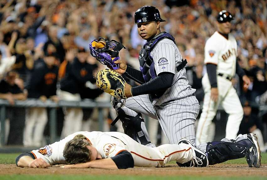 SAN FRANCISCO, CA - SEPTEMBER 27: Conor Gillaspie #50 of the San Francisco Giants lay face down at home plate after hitting an inside the park two-run home run as catcher Wilin Rosario #12 of the Colorado Rockies looks on in the seventh inning at AT&T Park on September 27, 2011 in San Francisco, California. (Photo by Thearon W. Henderson/Getty Images)