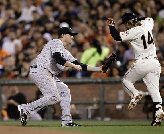 Colorado Rockies first baseman Jordan Pacheco, left, tags out San Francisco Giants' Mike Fontenot after being drawn off base by a wide throw during the third inning of a baseball game in San Francisco,  Tuesday, Sept. 27, 2011. (AP Photo/Marcio Jose Sanchez) Photo: Marcio Jose Sanchez, AP