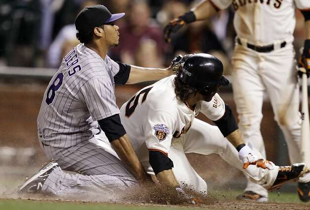 San Francisco Giants' Brandon Crawford, right, scores after a wild pitch by Colorado Rockies reliever Esmil Rogers, left, during the sixth inning of a baseball game in San Francisco, Tuesday, Sept. 27, 2011. (AP Photo/Marcio Jose Sanchez) Photo: Marcio Jose Sanchez, AP