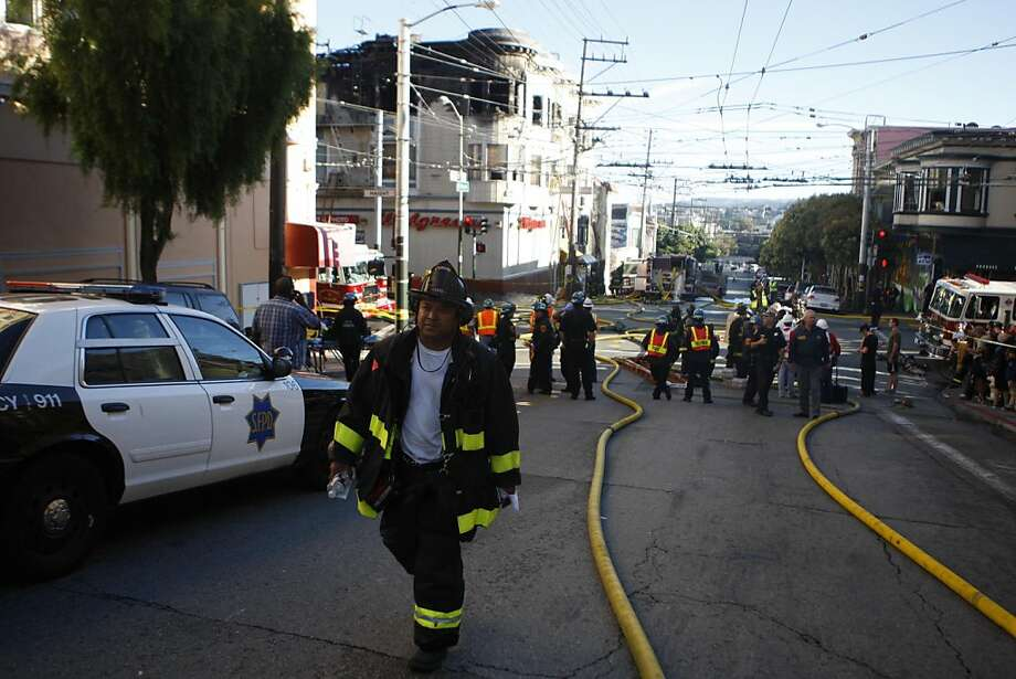 A firefighter walks up Fillmore St. after helping douse a fire in a building on the corner of Haight St. and Fillmore St. in San Francisco, Calif., on Tuesday, Sept. 27, 2011. Photo: Dylan Entelis, The Chronicle