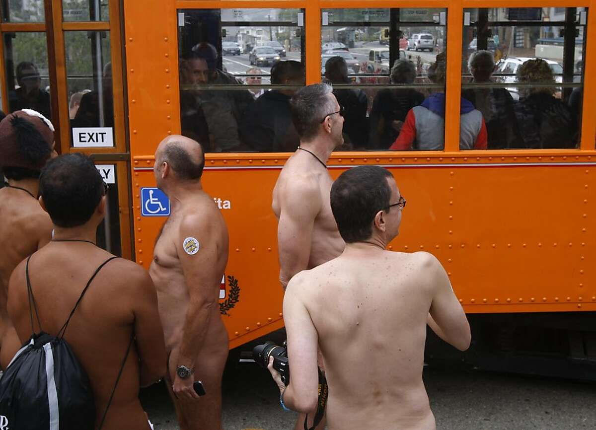 A Muni F-Market line streetcar rolls past nudists at Castro and 17th streets in San Francisco.