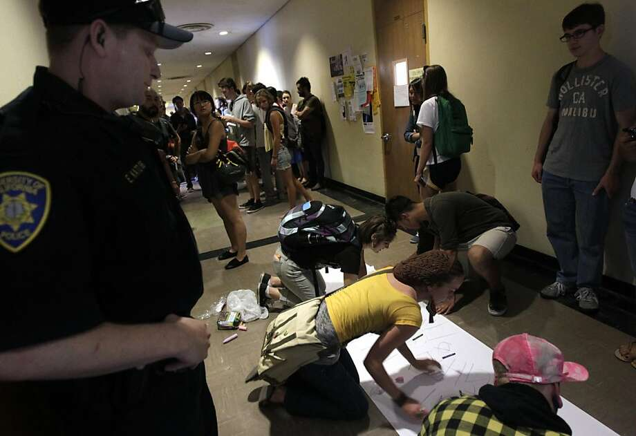 A UC police officer watches protesters leave messages on paper during an occupation of Tolman Hall at UC Berkeley campus  on Thursday, Sept. 22, 2011. Photo: Paul Chinn, The Chronicle