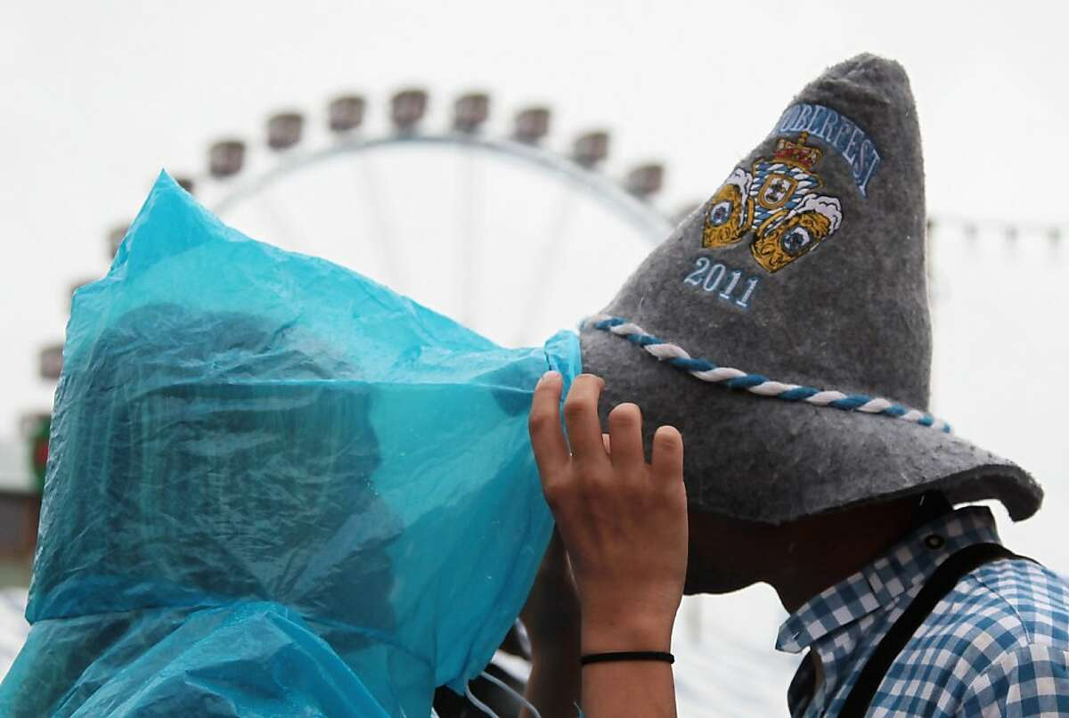 MUNICH, GERMANY - SEPTEMBER 18: Revellers covered against rain try to kiss each other during day 2 of the Oktoberfest 2011 beer festival at Theresienwiese on September 18, 2011 in Munich, Germany. (Photo by Johannes Simon/Getty Images)