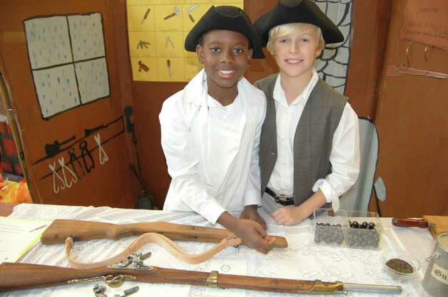 Brunswick School 4th graders Cedric Lafleur, left, and Thomas Doster take on the identities of colonial tradesmen living in Hingham, Massachusetts circa 1764, as they man their colonial gunsmith booth during the recent Colonial Day celebration at the school. Photo: Contributed Photo