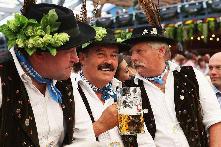 MUNICH, GERMANY - SEPTEMBER 17:  Three man wearing traditional Bavarian dresses chat during the open