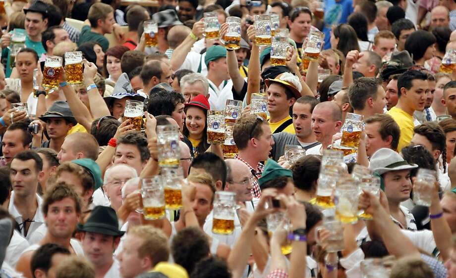 "Visitors lift up their beer steins after the official opening of the famous Bavarian ""Oktoberfest"" beer festival in a beer tent in Munich, southern Germany, Saturday, Sept. 17, 2011. The world's largest beer festival, runs from Sept. 17 to Oct. 3, 2011. (AP Photo/Matthias Schrader) Photo: Matthias Schrader, AP"