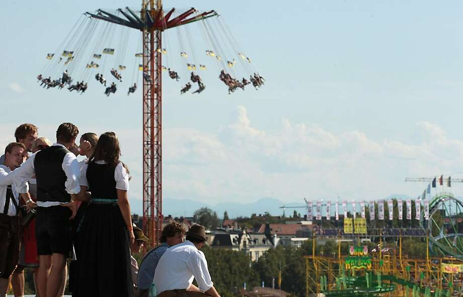 MUNICH, GERMANY - SEPTEMBER 17:  Revellers enjoy the view over the Oktoberfest from the top of the roof of a nearby house during the opening day of the Oktoberfest 2011 beer festival at Theresienwiese on September 17, 2011 in Munich, Germany.  (Photo by Johannes Simon/Getty Images) Photo: Johannes Simon, Getty Images