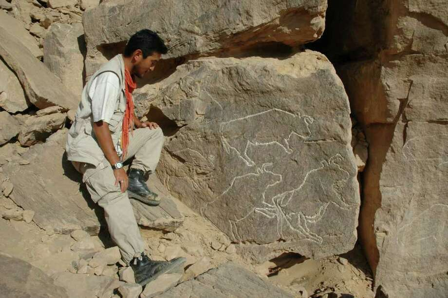 Belgian archaeologist Wouter Claes, a member of the research team, poses with a carving of wild cattle at the site near Quarta, Egypt. The art, from the late Palaeolithic period is the oldest art found in Egypt so far. Photo: Contributed Photo / Connecticut Post Contributed