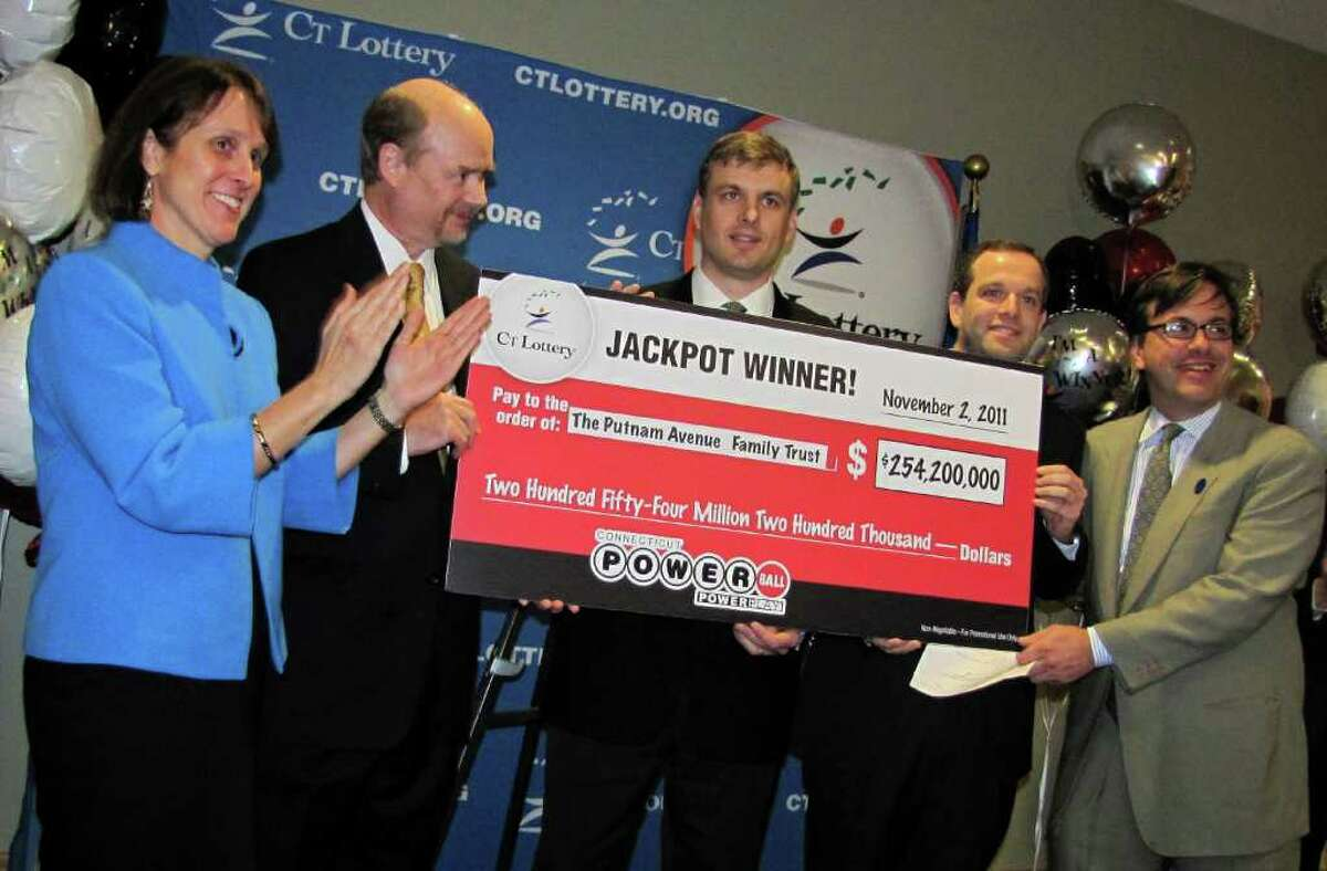 In this photo provided by the Connecticut Lottery, Greenwich, Conn. wealth managers Tim Davidson, second left, Greg Skidmore, center, and Brandon Lacoff, second right, pose Monday, Nov. 28. 2011 with a ceremonial check after the men claimed a $254.2 million Powerball jackpot the won on Nov. 2, in Rocky Hill, Conn. The jackpot was the largest ever won in Connecticut and the 12th biggest in Powerball history. The largest previous lottery jackpot in Connecticut was $59.5 million in June 2005. (AP Photo/Connecticut Lottery via the Stamford Advocate)