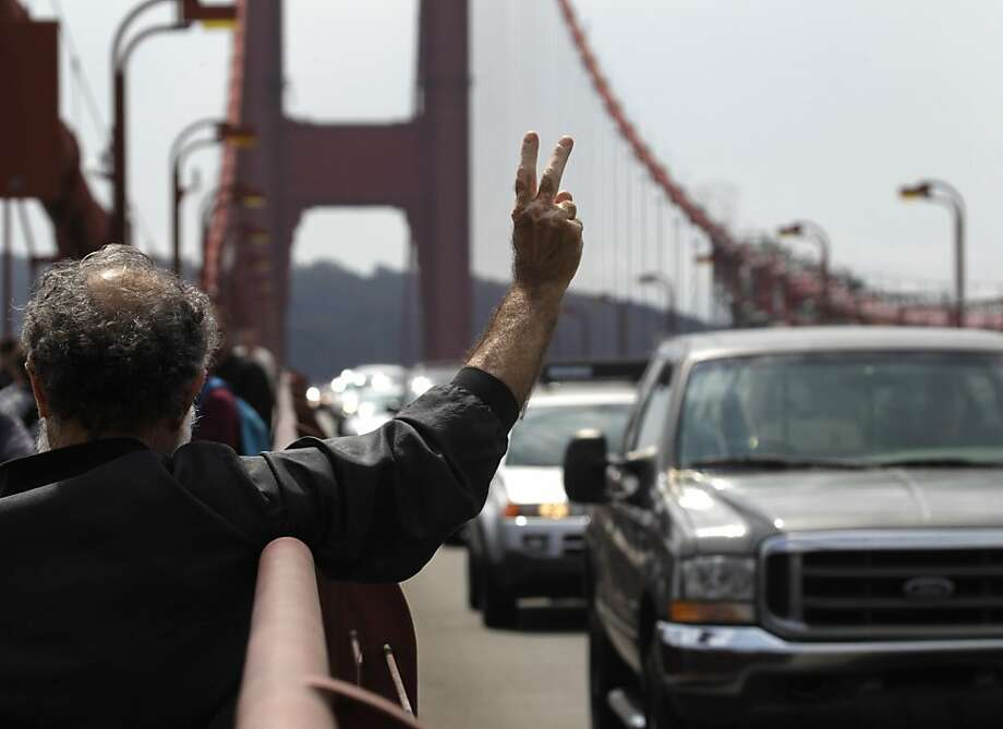 Angelo Douvos solicits support from passing cars during a peace rally on the Golden Gate Bridge in San Francisco, Calif. on Sunday, Sept. 11, 2011. Photo: Paul Chinn, The Chronicle