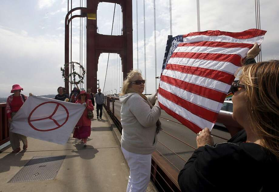 "Trisha Mills (center) and Jeanette Given wave the U.S. flag while peace activists (left) march across the Golden Gate Bridge in San Francisco, Calif. on Sunday, Sept. 11, 2011, as part of a national campaign called ""Create, Not Hate"". The march was held to commemorate the tenth anniversary of the 9/11 attack and to call for an end to the war in Iraq and Afghanistan. Photo: Paul Chinn, The Chronicle"