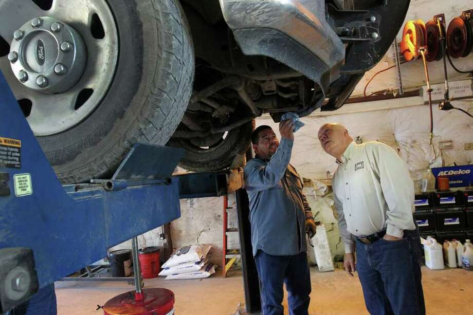 Harry Levy, (right) owner of the Levy Co. LP, inspects the underside of a truck with shop foreman Robert Cruz. Levy has faced challenges hiring qualified workers because of jobs in the Eagle Ford Shale. Photo: JOHN DAVENPORT, SAN ANTONIO EXPRESS-NEWS / SAN ANTONIO EXPRESS-NEWS (Photo can be sold to the public)
