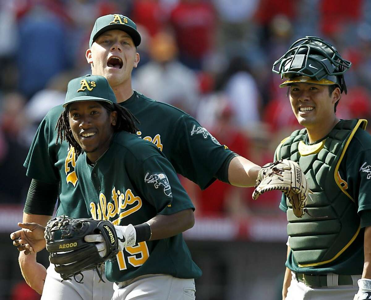 Oakland Athletics second baseman Jemile Weeks, from left, relief pitcher Andrew Bailey and catcher Kurt Suzuki celebrates their win against the Los Angeles Angels during a baseball game in Anaheim, Calif., Sunday, Sept. 25, 2011. (AP Photo/Chris Carlson)