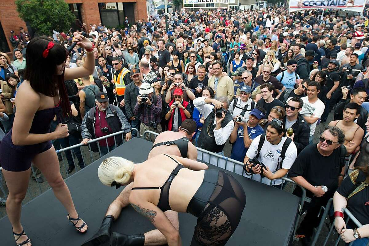 People watch a man being flogged on a stage during the Folsom Street Fair 2011 on September 25, 2011 in San Francisco, Calif.