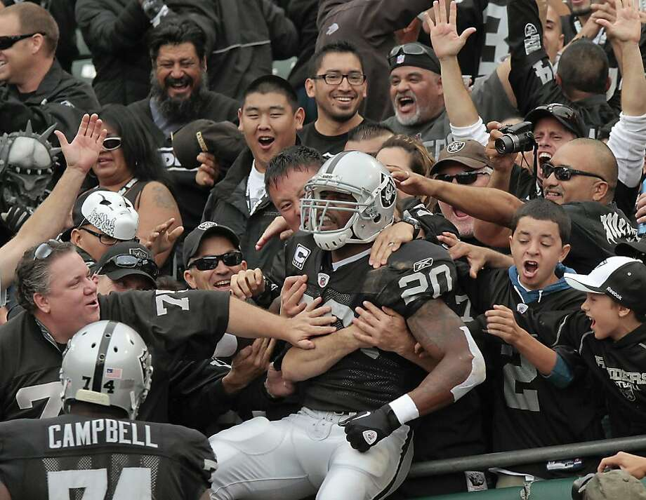 Raider fans hug Darren McFadden after his 1st quarter touchdown  against the Jets in Oakland, Calif. on Sunday, Sept. 25, 2011. Ran on: 09-26-2011 Darren McFadden lifted the Raiders with 171 yards and two touchdowns Sunday. Fans return the favor. Photo: John Storey, Special To The Chronicle