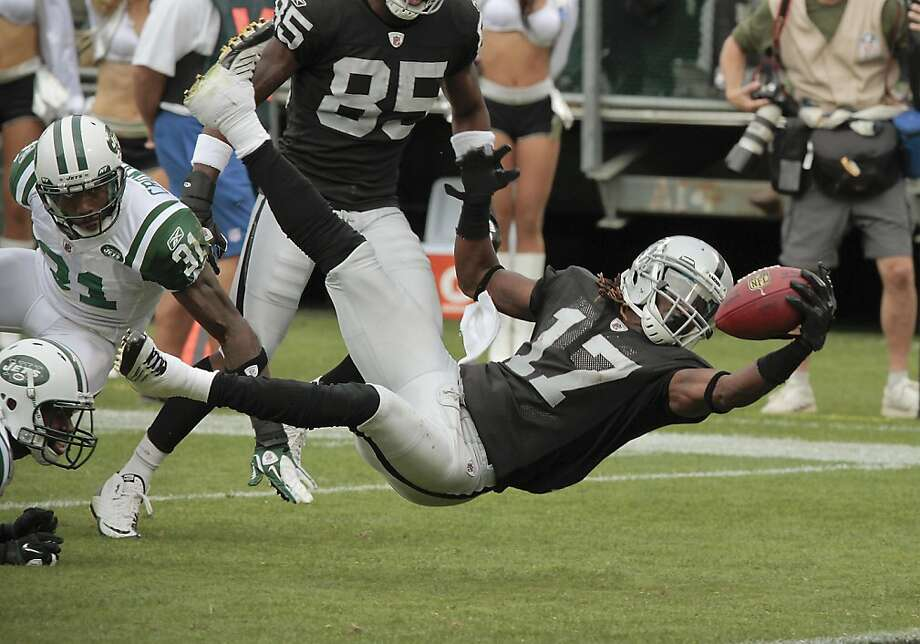 Raider receiver Denarius Moore puts the ball into the end zone for a touchdown against the Jets in Oakland, Calif., on Sunday, September 25,  2011.  Ran on: 09-26-2011 Raiders receiver Denarius Moore extends the ball over the goal line for the go-ahead touchdown in the third quarter. Moore picked up 23 yards on a slow-developing reverse. Ran on: 09-26-2011 Raiders receiver Denarius Moore extends the ball over the goal line for the go-ahead touchdown in the third quarter. Moore picked up 23 yards on a slow-developing reverse. Photo: John Storey, Special To The Chronicle