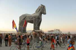 "People gather around the Trojan Horse at it is pulled across the ""playa"" at the Burning Man festival in Gerlach, Nev. on Friday, Sept. 2, 2011. (AP Photo/Reno Gazette-Journal, Andy Barron)"