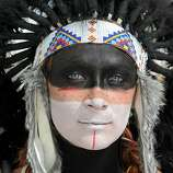 Katrina Van-Marter of Texas wears makeup and a feather headdress at the Burning Man festival in Gerlach, Nev. on Friday, Sept. 2, 2011. (AP Photo/Reno Gazette-Journal, Andy Barron)