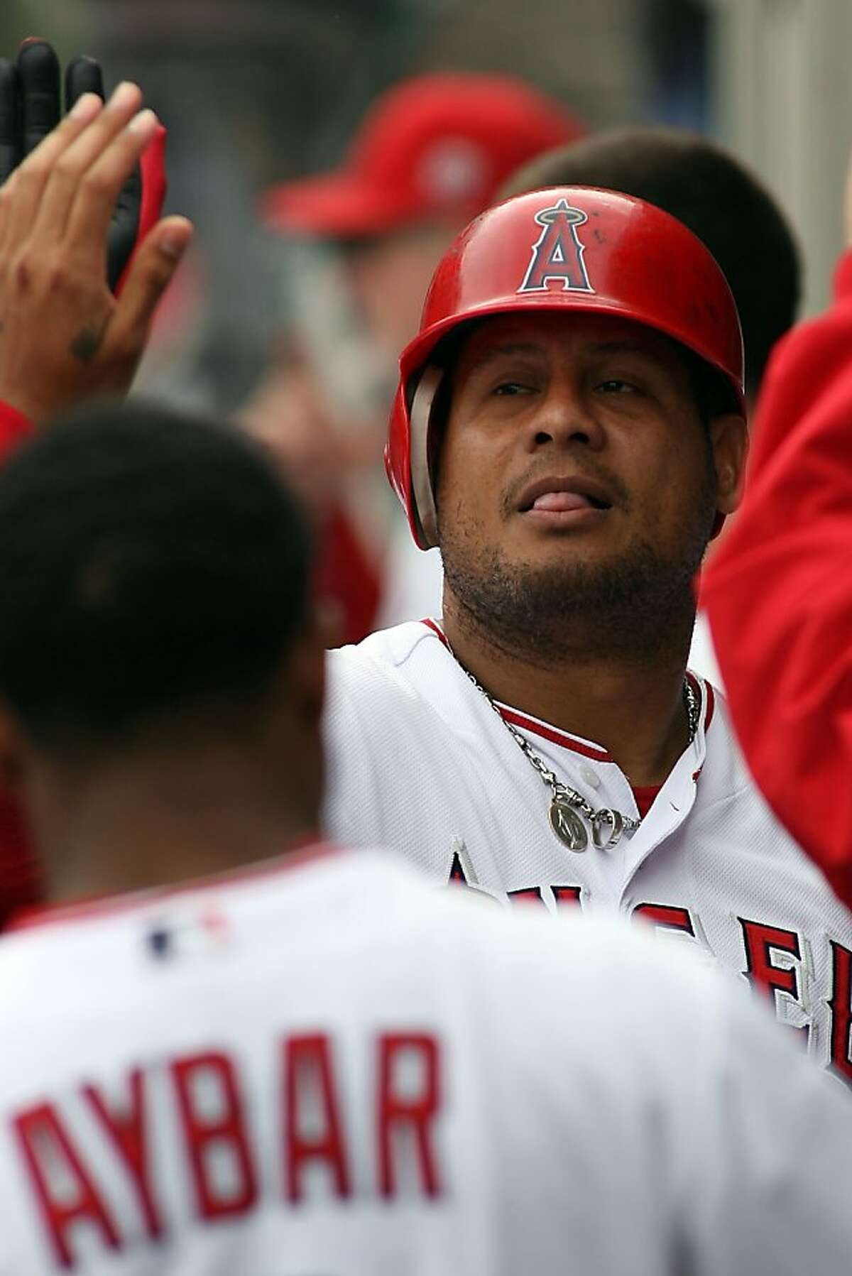 ANAHEIM, CA - SEPTEMBER 25: Bobby Abreu #53 of the Los Angeles Angels of Anaheim high-fives teammates in the dugout after hitting a solo home run against the Oakland Athletics in the third inning at Angel Stadium of Anaheim on September 25, 2011 in Anaheim, California. (Photo by Jeff Golden/Getty Images)