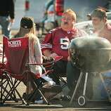 A group of 49er fans cooking on the weber outside Candlestick Park before the 49er-Texans game in San Francisco, Calif., on August 26th, 2011.