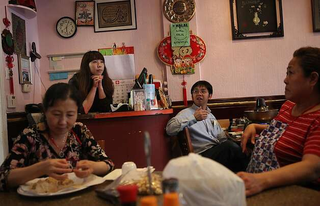 Clockwise--Yong Wan shredding chicken for salad, Didi Wu waiting for customers behind the counter, customer Jackie Huang watching television as well as pastry chef Xiu De Guo (right) watching television at the Old Mandarin Islamic restaurant, 3132 Vicente St., in San Francisco, California, on Wednesday, September 21, 2011. Photo: Liz Hafalia, The Chronicle