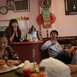 Clockwise--Yong Wan shredding chicken for salad, Didi Wu waiting for customers behind the counter, customer Jackie Huang watching television as well as pastry chef Xiu De Guo (right) watching television at the Old Mandarin Islamic restaurant, 3132 Vicente St., in San Francisco, California, on Wednesday, September 21, 2011.