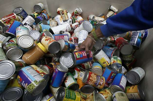 A woman from a local church looks through a bin of canned goods at the food bank. The San Francisco Food Bank has many customers including the Holley Court apartments in the outer Mission District.  Resident Herman Travis distributes the food bank food to seniors and disabled people in the apartment complex Tuesday November 16, 2010. Photo: Brant Ward, The Chronicle 2010