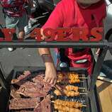 Eli Bequepps of Milpitas cooks Carne Asada and Chipotle Chicken at Candlestick Park before the 49er-Texans game in San Francisco, Calif., on August 26th, 2011.