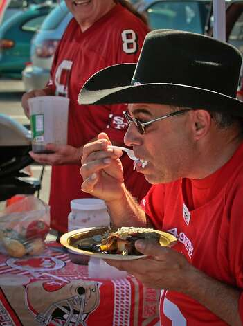 John Gould of San Francisco  has a bite of some food at a tailgate party outside Candlestick Park before the 49er-Texans game in San Francisco, Calif., on August 26th, 2011. Photo: John Storey, Special To The Chronicle