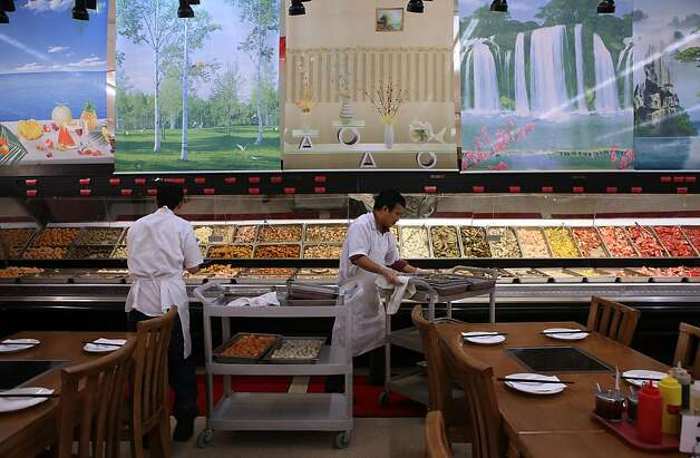 Buffet manager Vincent Xu (left) and Ye Lang Zhang (right) adding fresh meat and vegetables to the buffet at Oceanview Supermarket  in San Francisco, California, on Wednesday, August 31, 2011. Photo: Liz Hafalia, The Chronicle