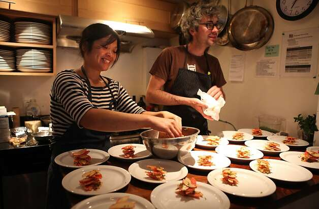 Head chef Linh Phu plating pink pearl and gala apple slaw for the producer dinner featuring Cowgirl Creamery cheeses at 18 Reasons in San Francisco, Calif., on Friday, August 19, 2011.  Butcher Morgan Maki helping at right. Photo: Liz Hafalia, The Chronicle