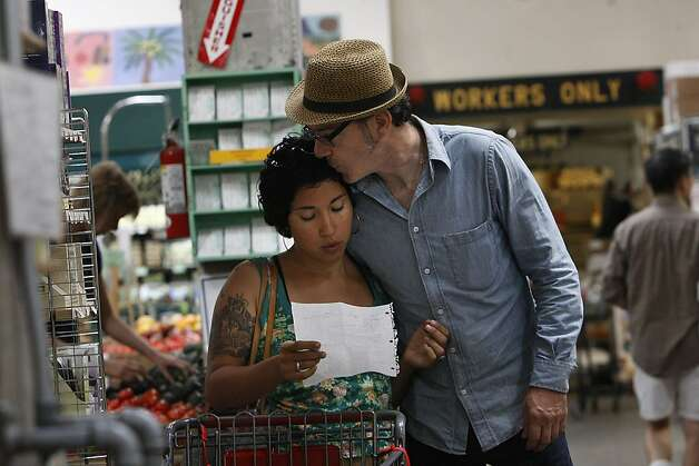 Francine Madrid checking her shopping list as Tim Lilly kisses her while shopping at Rainbow Grocery Cooperative in San Francisco, California, on Monday, September 19, 2011. Photo: Liz Hafalia, The Chronicle