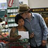 Francine Madrid checking her shopping list as Tim Lilly kisses her while shopping at Rainbow Grocery Cooperative in San Francisco, California, on Monday, September 19, 2011.