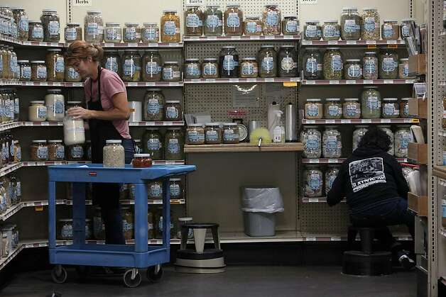 Geri Smessaert (left) cleaning herb jars at Rainbow Grocery Cooperative in San Francisco, California, on Monday, September 19, 2011. Photo: Liz Hafalia, The Chronicle