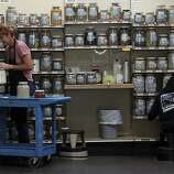 Geri Smessaert (left) cleaning herb jars at Rainbow Grocery Cooperative in San Francisco, California, on Monday, September 19, 2011.