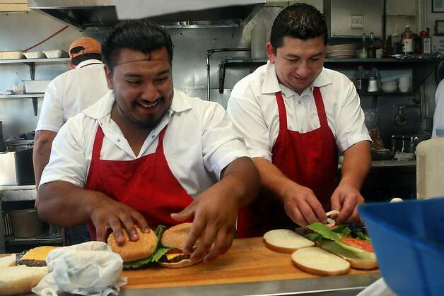 Cooks Cesar Candry (left) and  Ernesto Monge (right) helping to prepare 19 burgers at the Java House just before a Giant's game in San Francisco, Calif.,  on Sunday, August 28, 2011. Photo: Liz Hafalia, The Chronicle