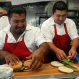 Cooks Cesar Candry (left) and  Ernesto Monge (right) helping to prepare 19 burgers at the Java House just before a Giant's game in San Francisco, Calif.,  on Sunday, August 28, 2011.
