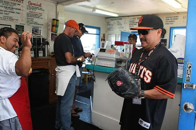 Cook Cesar Candry (left) playing with customer Robert Jimenez (right), from San Francisco  at the Java House during the beginning of a Giant's game in San Francisco, Calif.,  on Sunday, August 28, 2011. Photo: Liz Hafalia, The Chronicle