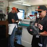 Cook Cesar Candry (left) playing with customer Robert Jimenez (right), from San Francisco  at the Java House during the beginning of a Giant's game in San Francisco, Calif.,  on Sunday, August 28, 2011.