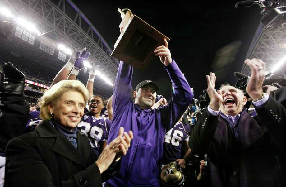 Washington coach Steve Sarkisian, center, lifts the Apple Cup trophy after being given it by Gov. Chris Gregoire, left, as school president Michael Young applauds after the team defeated Washington State in an NCAA college football game on Saturday, Nov. 26, 2011, in Seattle. Washington won 38-21. Photo: AP
